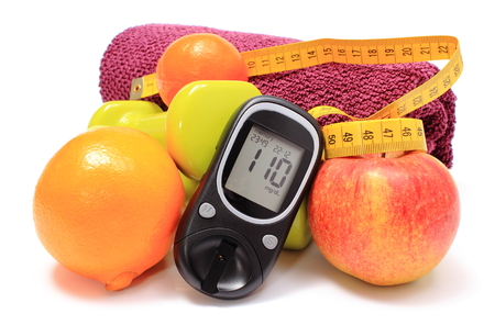 Glucometer, fresh fruits, tape measure, dumbbells and purple towel for using in fitness, concept for diabetes, slimming, lifestyle and healthy nutrition photo