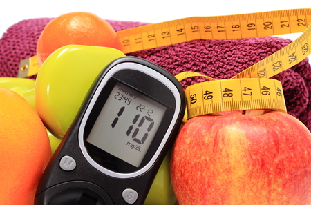 Glucose meter, fresh fruits, tape measure, dumbbells and purple towel for using in fitness, concept for diabetes, slimming, lifestyle and healthy nutrition photo