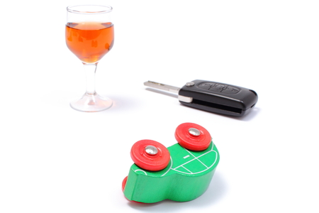 Overturned wooden toy car with glass of wine and car key, car key and alcohol, don photo