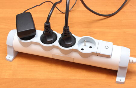 surge: Electrical plugs with cords connected to electrical power strip, electrical extension for appliances with On-Off switch, concept of energy saving Stock Photo