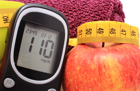 Glucometer, fresh apple and tape measure, concept for diabetes, lifestyle and healthy nutrition