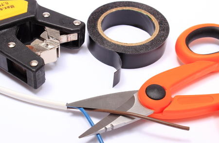 cable cutter: Cable cutter, electric wire and black insulating tape on white background, accessories for engineer jobs and repair of electrical cable
