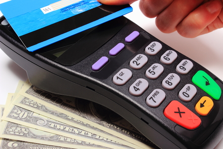 contactless: Hand of woman paying with contactless credit card with NFC technology, credit card reader, payment terminal and cash, finance concept