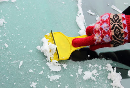 scraping: Hand of woman in glove scraping ice and snow from car windscreen