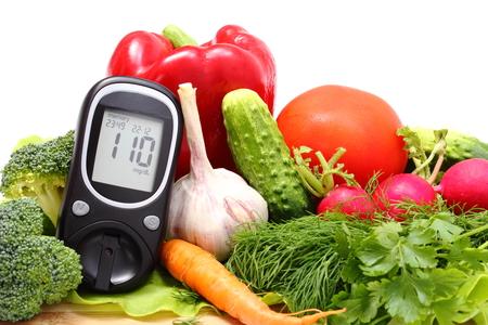 diabetes: Medidor de glucosa y verduras crudas frescas y maduras que mienten en la tabla de cortar de madera