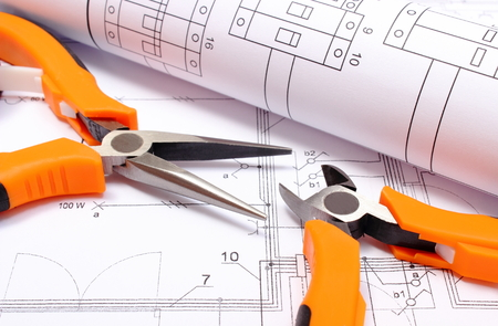 electrical engineering: Orange metal pliers with rolled electrical diagram lying on construction drawing of house