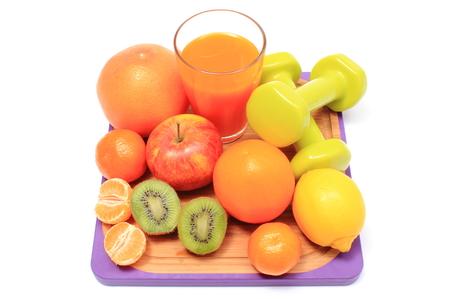 inmunidad: Frutas naturales frescas maduras, pesas para utilizar en el gimnasio y vaso de jugo, el concepto de adelgazamiento, la alimentaci�n sana y el fortalecimiento de la inmunidad