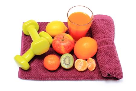 inmunidad: Frutas frescas, vaso de jugo y verde para el uso de pesas en el gimnasio acostada sobre una toalla de color p�rpura, el concepto de adelgazamiento, la alimentaci�n sana y el fortalecimiento de la inmunidad