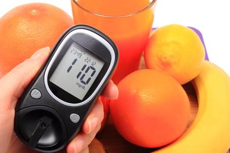 inmunidad: Mano con medidor de glucosa, frutas naturales frescas maduras y vaso de jugo, el concepto de la diabetes, la nutrici�n saludable y el fortalecimiento de la inmunidad