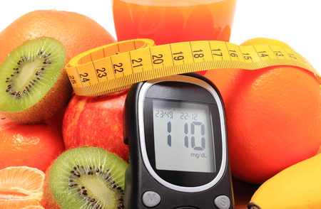 diabetes: Glucose meter, fresh ripe natural fruits with tape measure and glass of juice on cutting board, concept for diabetes, healthy nutrition and strengthening immunity Stock Photo