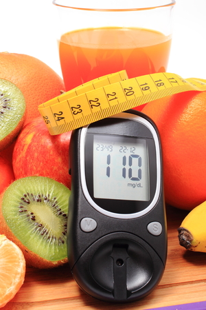 strengthening: Glucometer, fresh ripe natural fruits with tape measure and glass of juice on cutting board, concept for diabetes, healthy nutrition and strengthening immunity Stock Photo