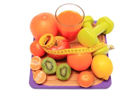 inmunidad: Frutas frescas, pesas para utilizar en el gimnasio, cinta m�trica y un vaso de jugo, el concepto de adelgazamiento, la alimentaci�n sana y el fortalecimiento de la inmunidad