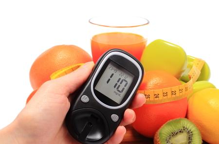 inmunidad: Gluc�metro en la mano. frutas frescas, pesas para utilizar en el gimnasio, cinta m�trica y un vaso de jugo, el concepto de la diabetes, de adelgazamiento, la alimentaci�n sana y el fortalecimiento de la inmunidad