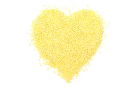 groats: Heart shaped yellow millet groats, valentine heart of millet groats. Isolated on white background