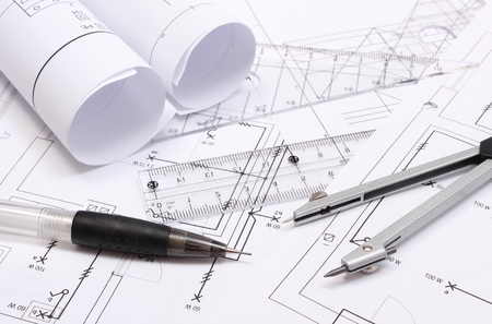 Rolled electrical diagrams and accessories for drawing lying on construction drawing of house, drawings and accessories for the projects engineer jobs