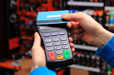 Hand of woman paying with contactless credit card with NFC technology in an electrical shop, credit card reader, payment terminal, finance concept Banque d'images
