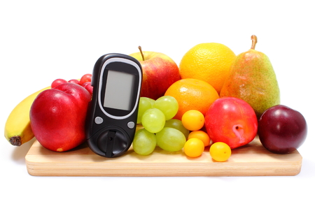 Glucose meter and fresh ripe fruits lying on wooden cutting board, concept for healthy eating and diabetes. Isolated on white background photo