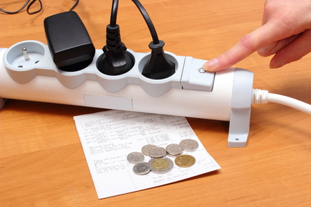 Finger of woman turns off electrical extension, electrical plugs connected to electrical power strip, electricity bill with coins, concept for energy saving