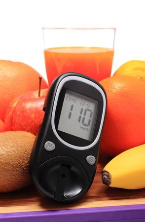 inmunidad: Medidor de glucosa, frutas naturales frescas maduras y vaso de jugo en la tabla de cortar, el concepto de la diabetes, la nutrici�n saludable y el fortalecimiento de la inmunidad