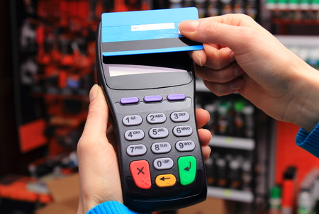 electronic card: Hand of woman paying with contactless credit card with NFC technology in an electrical shop, credit card reader, payment terminal, finance concept Stock Photo