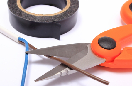 Cable cutter, electric wire and black insulating tape on white background, accessories for engineer jobs and repair of electrical cable photo