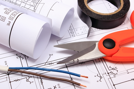 Cable cutter, electric wire and black insulating tape, rolls of electrical diagrams lying on construction drawing of house, accessories for engineer jobs