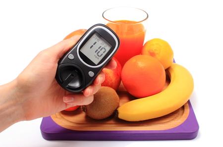 inmunidad: Mano con medidor de glucosa, frutas naturales frescas maduras y vaso de jugo en la tabla de cortar, el concepto de la diabetes, la nutrici�n saludable y el fortalecimiento de la inmunidad Foto de archivo