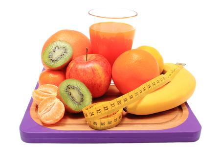 inmunidad: Frutas frescas maduras naturales, vaso de jugo y cinta m�trica en la tabla de cortar, el concepto de adelgazamiento, la alimentaci�n sana y el fortalecimiento de la inmunidad