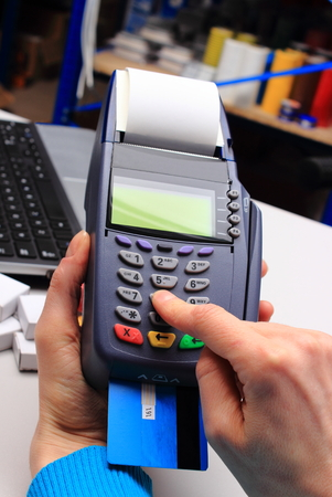 credit card payment: Hand of woman using payment terminal in an electrical shop, paying with credit card, credit card reader, finance concept Stock Photo
