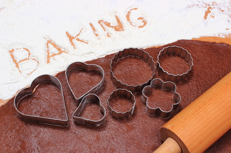 cookie cutters: Word baking written in white flour, cookie cutters and rolling pin on dough for cookies, concept for baking