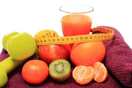 inmunidad: Frutas frescas con cinta m�trica, vaso de jugo y mancuernas verde para la aptitud extiende sobre una toalla de color p�rpura, el concepto de adelgazamiento, la alimentaci�n sana y el fortalecimiento de la inmunidad