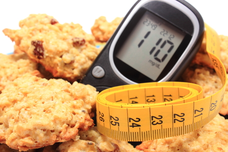 nutrition: Glucometer, oatmeal cookies and tape measure lying on colorful plate, concept for diabetes, slimming and healthy nutrition