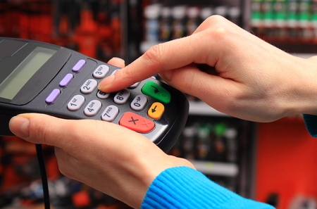 personal identification number: Hand of woman using payment terminal in an electrical shop, enter personal identification number, finance concept Stock Photo