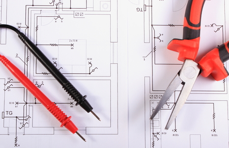 Cables of multimeter and metal pliers lying on electrical construction drawings of house, electrical drawings and tools for engineer jobs