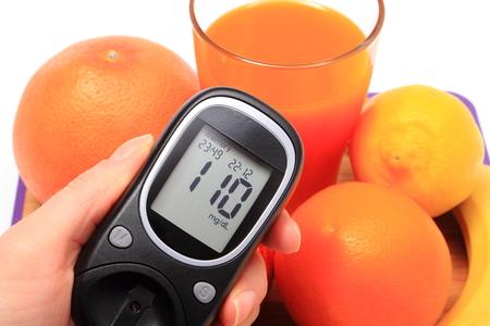 inmunidad: Mano con gluc�metro, frutas naturales frescas maduras y vaso de jugo, el concepto de la diabetes, la nutrici�n saludable y el fortalecimiento de la inmunidad