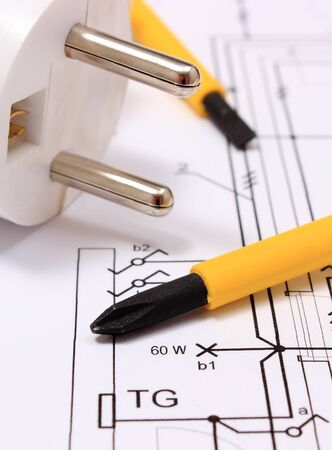 energy work: Screwdriver, work tools and electric plug lying on construction drawing of house, accessories for engineering work, energy concept