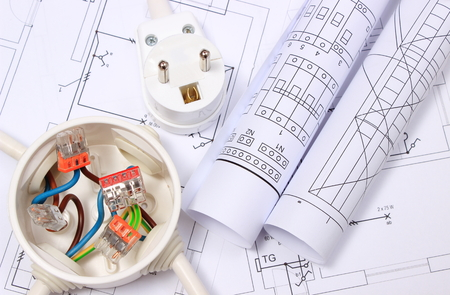 Copper wire connections in electrical box, electric plug and rolls of electrical diagrams on construction drawing of house, energy concept Stock Photo