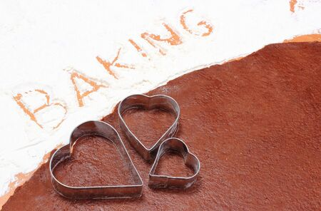 cookie cutters: Cookie cutters and word baking written in white flour, accessories and concept for baking, Stock Photo