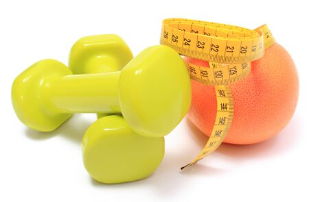 are slim: Green dumbbells for using in fitness, fresh grapefruit and tape measure, concept for slimming, healthy nutrition and lifestyle. Isolated on white background