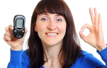 diabetes: Mujer sonriente que sostiene medidor de glucosa, que mide el nivel de azúcar, el concepto de la diabetes. Aislado en el fondo blanco