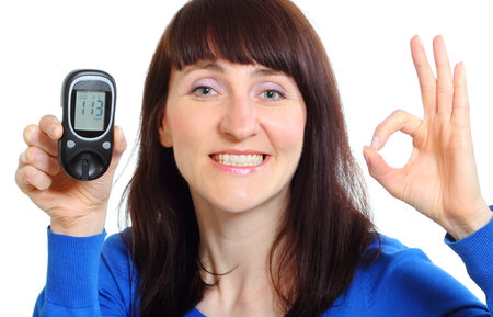 diabetes: Smiling woman holding glucose meter, measuring sugar level, concept for diabetes. Isolated on white background Stock Photo