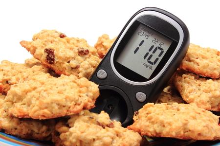 diabetes: Medidor de glucosa y galletas de avena que mienten en la placa de colorido, concepto para la diabetes y la nutrición saludable. Aislado en el fondo blanco Foto de archivo