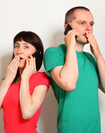 unexpected: Shocked woman and man receive an unexpected message while talking on mobile phone, hands covering mouth, face expression and human emotion