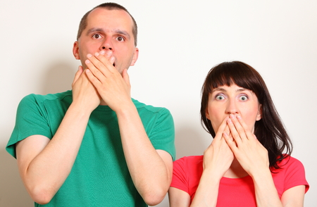 disturbing: Shocked and surprised woman and man, hands covering mouth, big eyes, face expression and human emotion