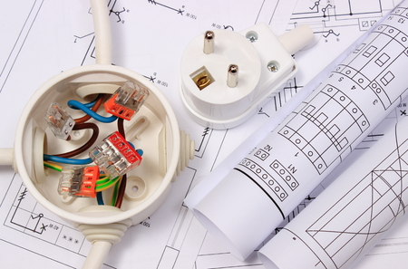 energy work: Copper wire connections in electrical box, rolls of electrical diagrams and electric plug on construction drawing of house, accessories for engineering work, energy concept Stock Photo