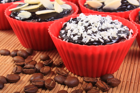 desiccated: Homemade delicious fresh baked chocolate muffins with desiccated coconut and sliced almonds in red silicone cups and coffee grains on wooden background, concept for dessert Stock Photo