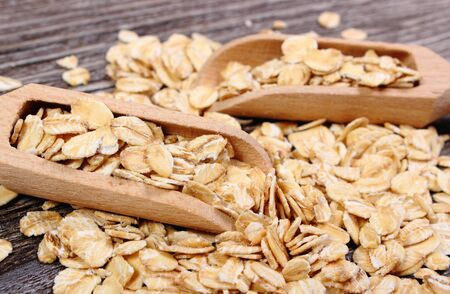 Heap of organic oatmeal, oat flakes with wooden spoon on wooden background, concept for healthy eating and nutrition photo