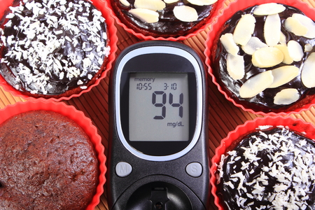 glucometer: Glucometer and homemade delicious fresh baked chocolate muffins in red silicone cups, concept for diabetes and dessert Stock Photo