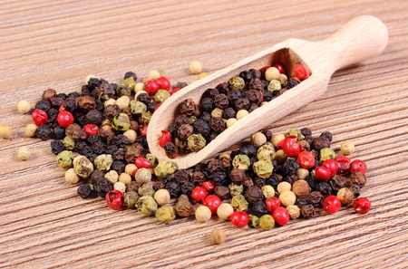 Heap of fresh colored pepper with wooden spoon lying on wooden table, seasoning for cooking, concept for healthy nutrition photo