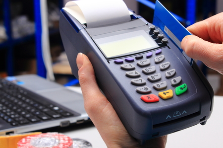 pagando: Mano de la mujer con el terminal de pago en una tienda de electrónica, pagando con tarjeta de crédito, lector de tarjetas de crédito, el concepto de finanzas